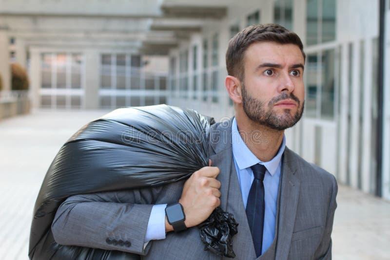 Hombre de negocios que sale de la oficina con la bolsa de plástico negra llena fotos de archivo libres de regalías