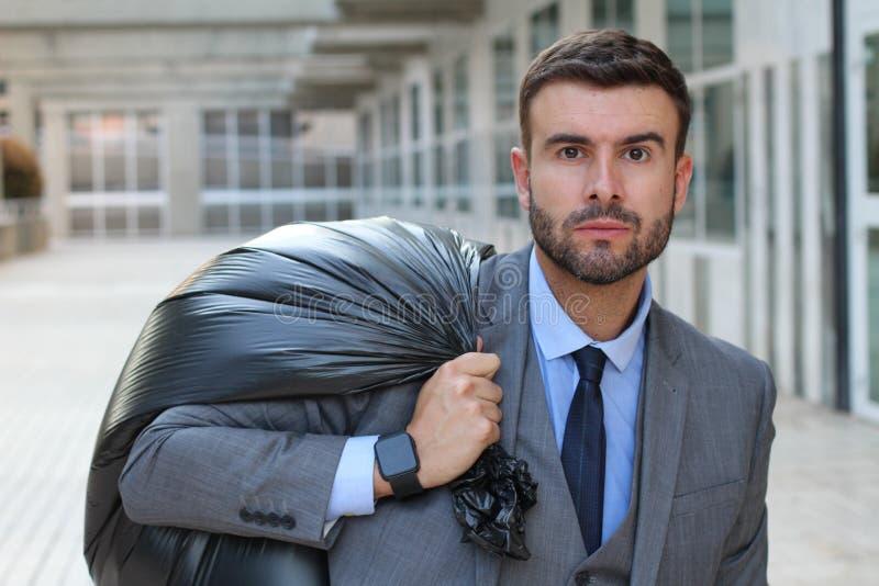Hombre de negocios que sale de la oficina con la bolsa de plástico negra llena imágenes de archivo libres de regalías