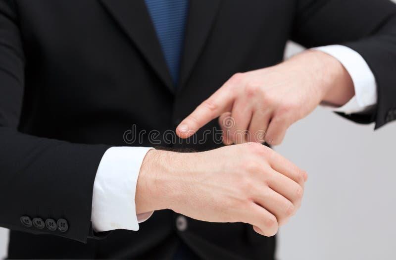 Hombre de negocios que señala algo en su mano foto de archivo