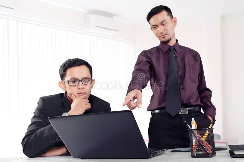 Hombre de negocios que señala el finger al ordenador portátil imágenes de archivo libres de regalías