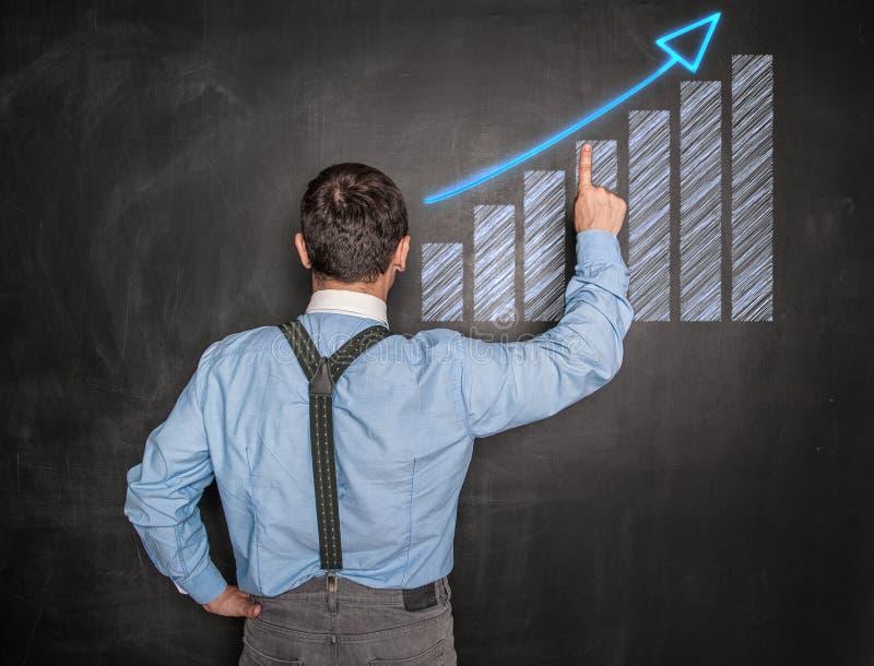 Hombre de negocios que señala el gráfico de la flecha en la pizarra imagen de archivo
