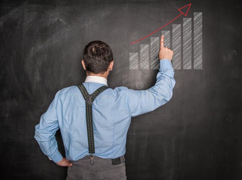Hombre de negocios que señala el gráfico de la flecha en la pizarra fotos de archivo libres de regalías