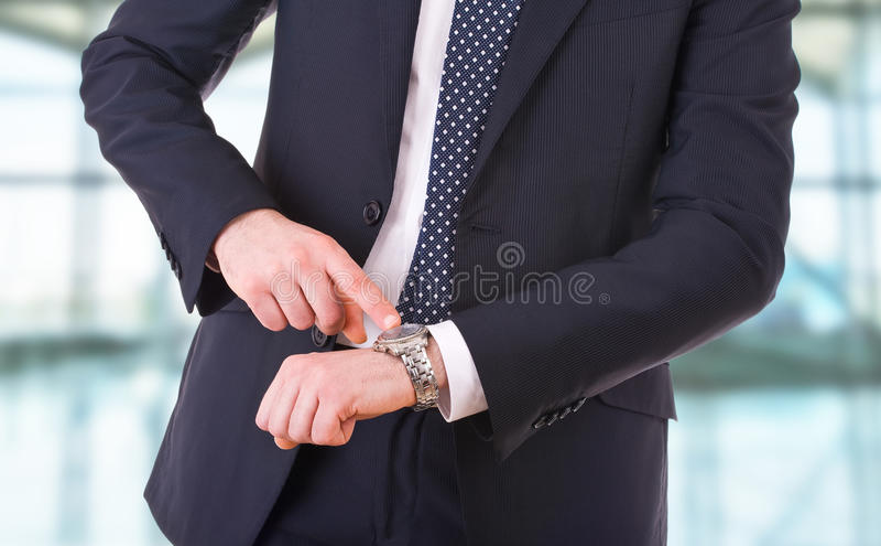 Hombre de negocios que señala en su reloj. imagen de archivo libre de regalías