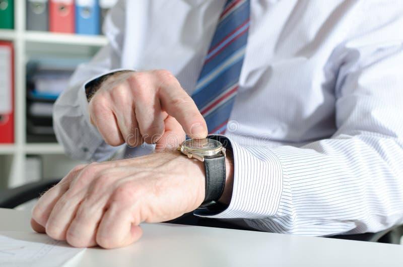 Hombre de negocios que señala su reloj con su finger fotos de archivo