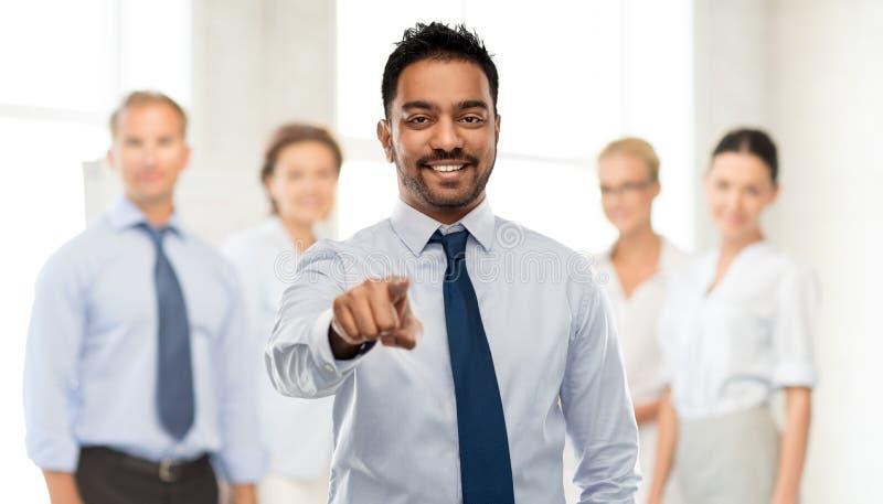 Hombre de negocios que señala a usted sobre el equipo del negocio foto de archivo