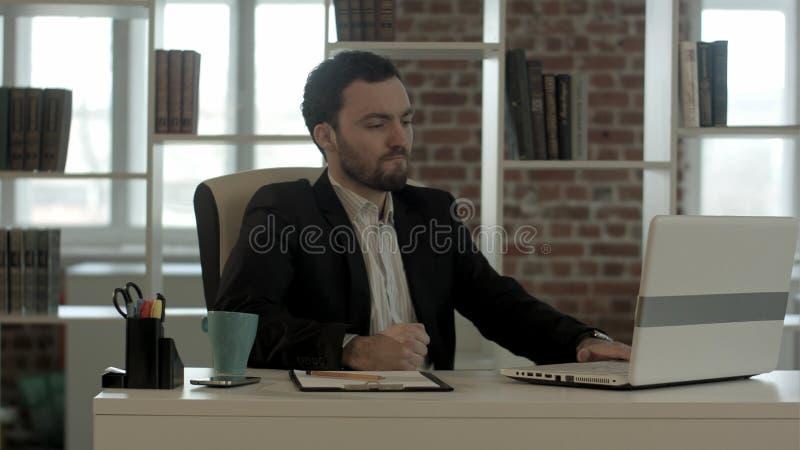 Hombre de negocios que se atierra en el horror que mira la pantalla del ordenador portátil imagen de archivo libre de regalías