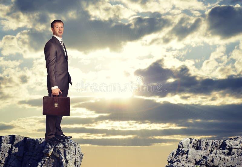 Hombre de negocios que se coloca al borde de hueco de la roca foto de archivo libre de regalías