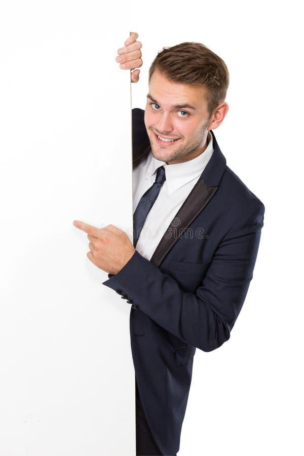 Hombre de negocios que se coloca al lado de una cartelera blanca en blanco imagenes de archivo