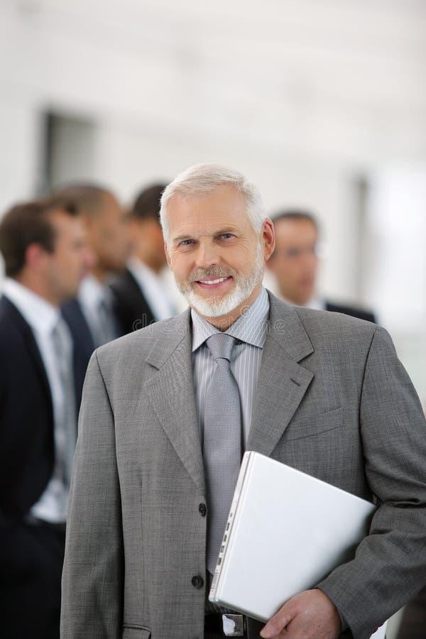 Hombre de negocios que se coloca con el laptopcomputer imagen de archivo libre de regalías