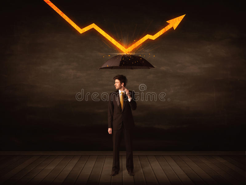 Hombre de negocios que se coloca con el paraguas que guarda la flecha anaranjada imagenes de archivo