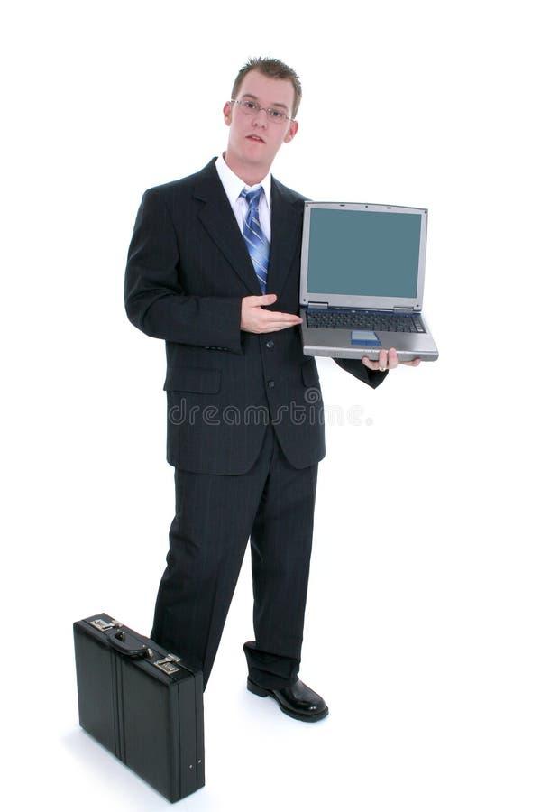 Hombre de negocios que se coloca con la cartera y la computadora portátil abierta fotos de archivo