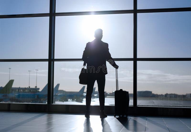 Hombre de negocios que se coloca con la maleta en aeropuerto foto de archivo libre de regalías