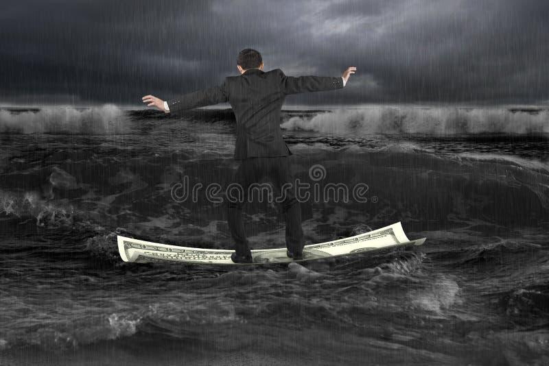 Hombre de negocios que se coloca de equilibrio en el barco del dinero que flota en Oc oscuro fotografía de archivo libre de regalías