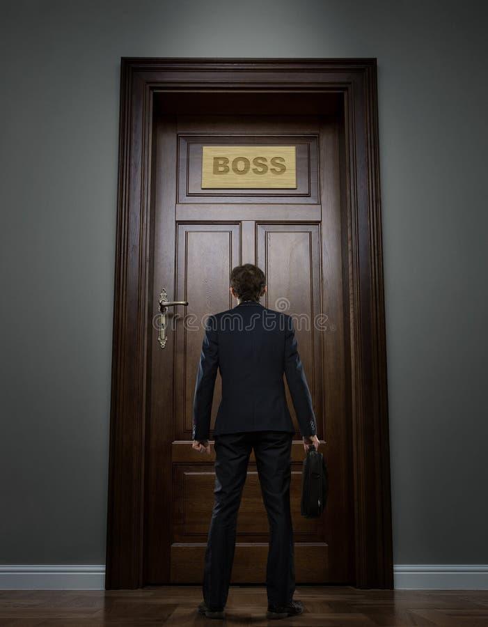 Hombre de negocios que se coloca delante de la puerta enorme imágenes de archivo libres de regalías