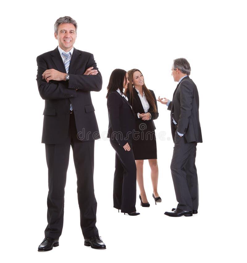 Hombre de negocios que se coloca delante de sus colegas fotografía de archivo
