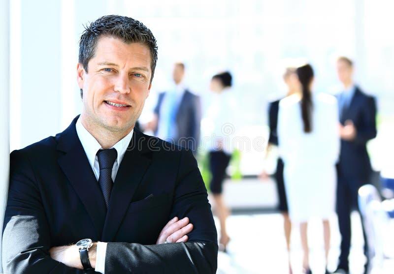Hombre de negocios que se coloca delante de sus colegas en oficina fotografía de archivo