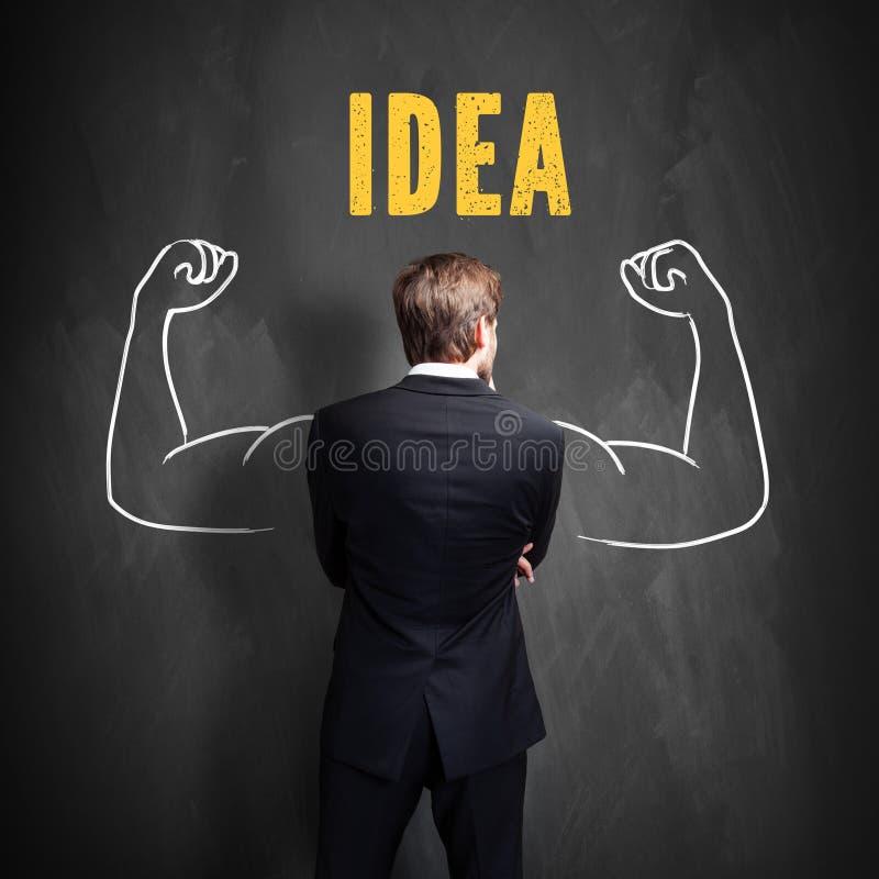 Hombre de negocios que se coloca delante de una pizarra con el ` del ` IDEA de la palabra foto de archivo libre de regalías