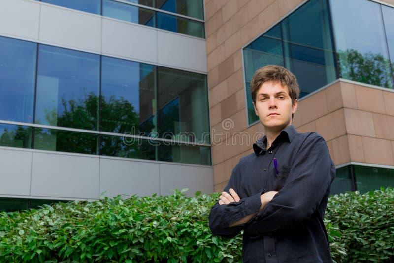 Hombre de negocios que se coloca delante del edificio de oficinas imágenes de archivo libres de regalías