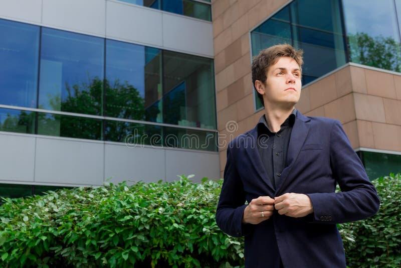 Hombre de negocios que se coloca delante del edificio de oficinas imagen de archivo libre de regalías