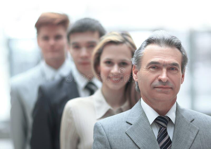 Hombre de negocios que se coloca delante de su equipo del negocio en fondo borroso de la oficina fotografía de archivo libre de regalías