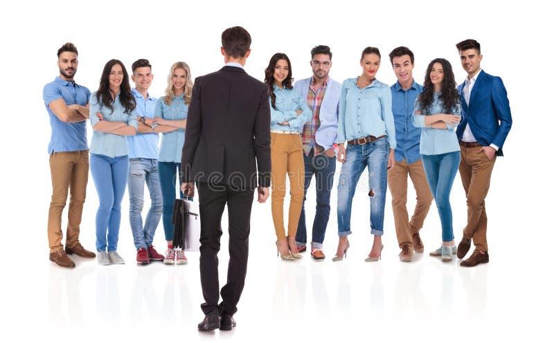 Hombre de negocios que se coloca delante de su equipo, mirándolos fotografía de archivo