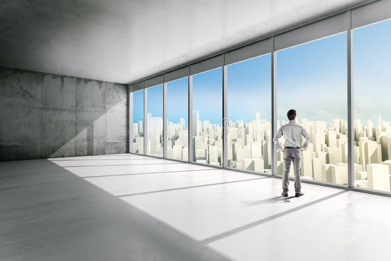Hombre de negocios que se coloca dentro de un edificio de oficinas fotografía de archivo libre de regalías
