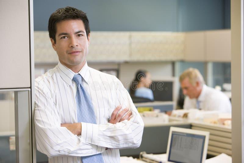 Hombre de negocios que se coloca en cubículo foto de archivo