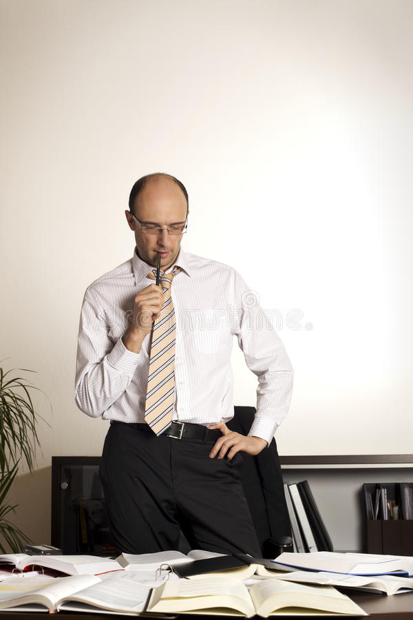 Hombre de negocios que se coloca en el escritorio de oficina foto de archivo libre de regalías