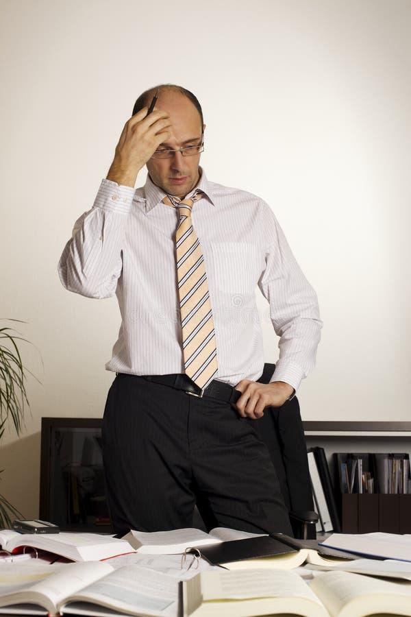 Hombre de negocios que se coloca en el escritorio de oficina, V2 imágenes de archivo libres de regalías