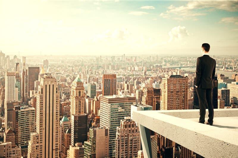 Hombre de negocios que se coloca en el tejado de un rascacielos y que mira el ove fotografía de archivo libre de regalías