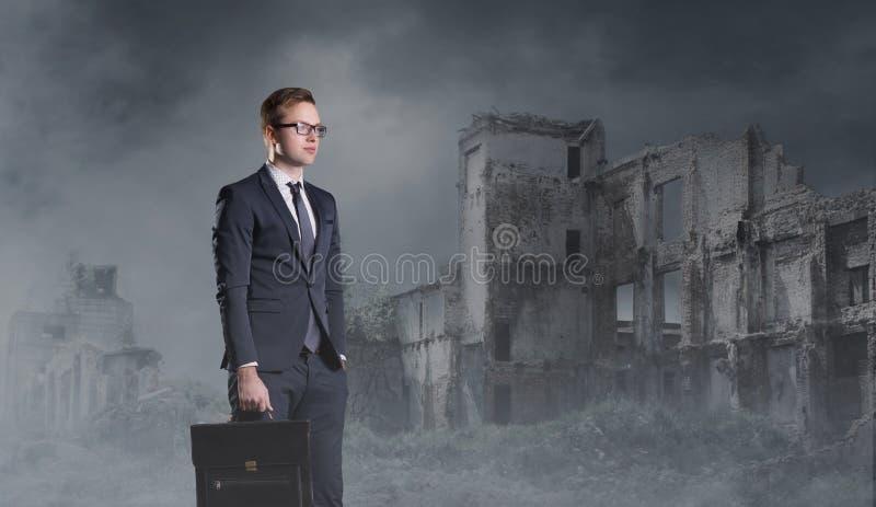 Hombre de negocios que se coloca en fondo apocalíptico Crisis, defecto, fotografía de archivo