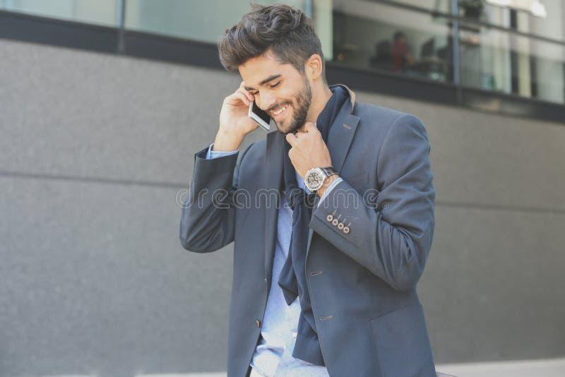 Hombre de negocios que se coloca en la calle y que habla en pho elegante foto de archivo libre de regalías