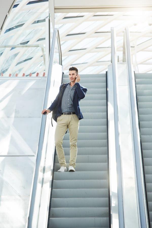 Hombre de negocios que se coloca en la escalera móvil con el teléfono móvil imagen de archivo libre de regalías
