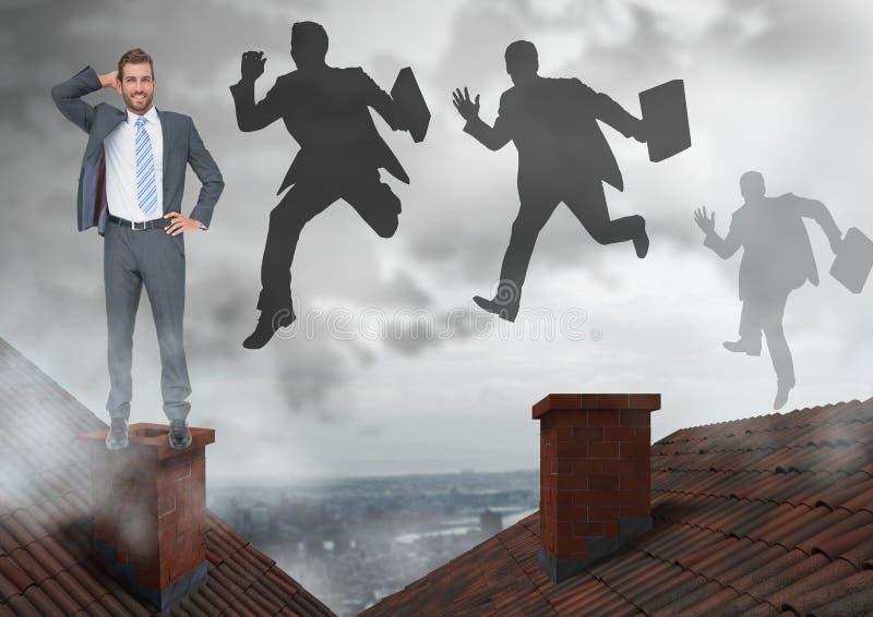 Hombre de negocios que se coloca en los tejados y las siluetas de los hombres de negocios que saltan con la chimenea y la ciudad  imagen de archivo libre de regalías