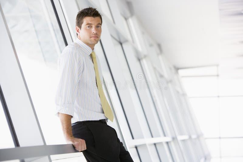 Hombre de negocios que se coloca en pasillo foto de archivo libre de regalías