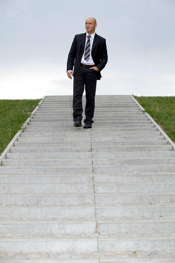 Hombre de negocios que se coloca en pasos de progresión fotografía de archivo