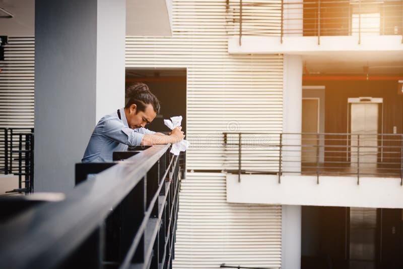 Hombre de negocios que se coloca en sitio de la oficina del balcón con el papel arrugado imágenes de archivo libres de regalías