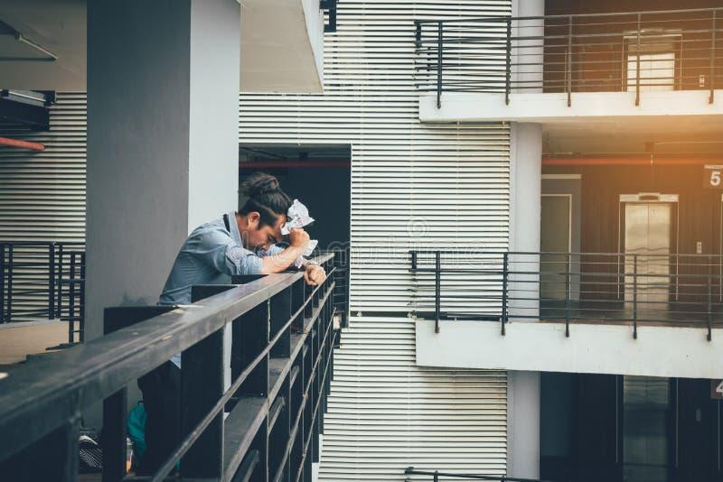 Hombre de negocios que se coloca en sitio de la oficina del balc?n con el papel arrugado foto de archivo libre de regalías