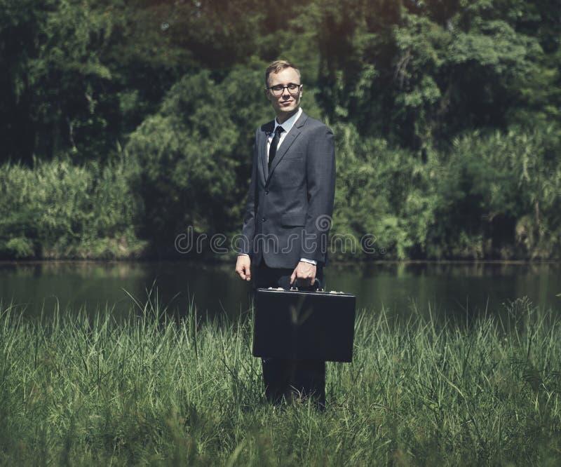 Hombre de negocios que se coloca en un prado foto de archivo