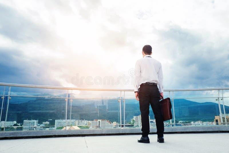 Hombre de negocios que se coloca en un tejado y que mira éxito de la ciudad y t fotos de archivo libres de regalías