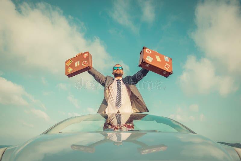 Hombre de negocios que se coloca en una playa cerca del coche fotografía de archivo