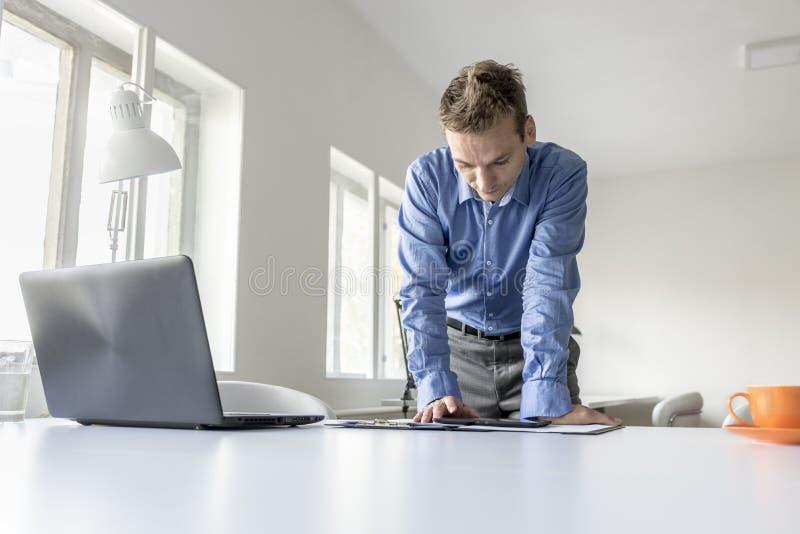 Hombre de negocios que se coloca que se inclina en su escritorio que lee un compu de la tableta imagen de archivo