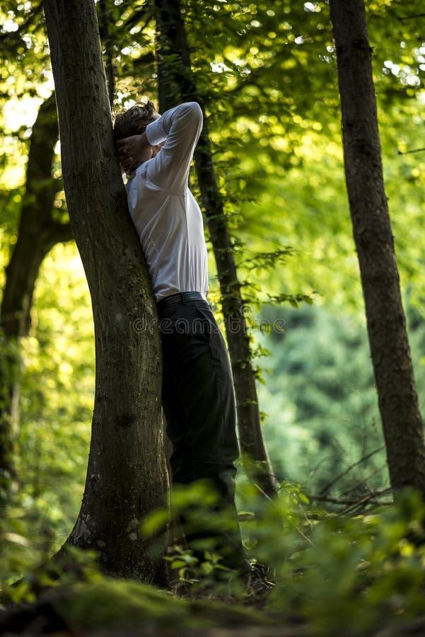 Hombre de negocios que se coloca que se inclina en un tronco de árbol imagen de archivo libre de regalías