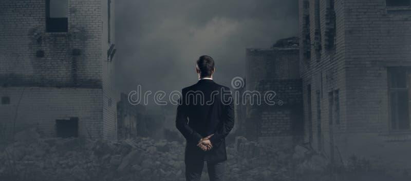 Hombre de negocios que se coloca sobre fondo apocalíptico Crisis, defaul fotografía de archivo libre de regalías