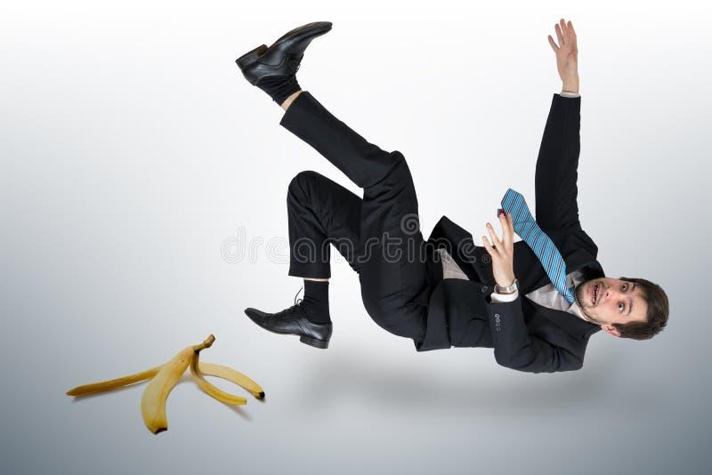 Hombre de negocios que se desliza en una cáscara del plátano fotos de archivo libres de regalías