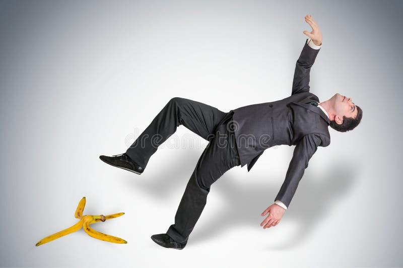 Hombre de negocios que se desliza y que cae de una cáscara del plátano imagen de archivo