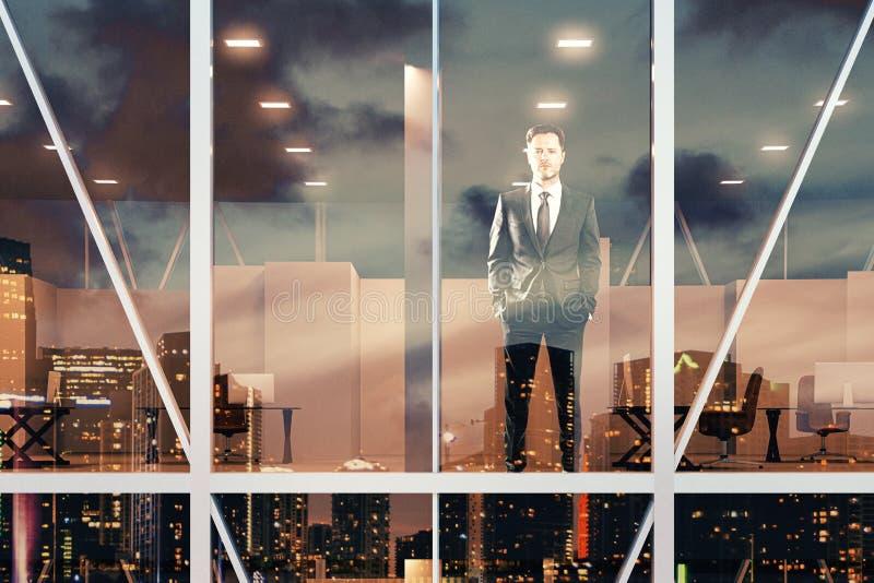 Hombre de negocios que se destaca y que mira la ventana de la oficina imagenes de archivo