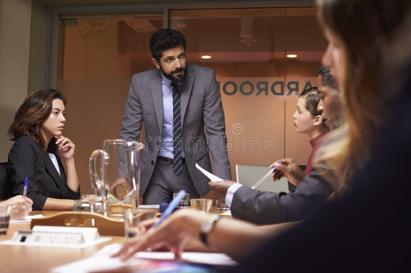 Hombre de negocios que se dirige al equipo en una reunión, cierre del ángulo bajo para arriba foto de archivo