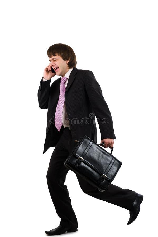 Hombre de negocios que se ejecuta y que habla por el teléfono fotos de archivo