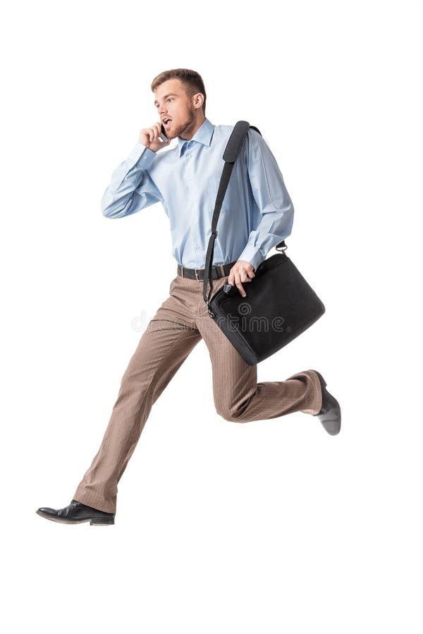 Hombre de negocios que se ejecuta y que habla por el teléfono fotos de archivo libres de regalías